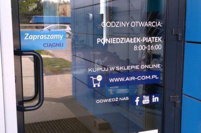 Napisy informacyjne i grafika na drzwiach wejściowych